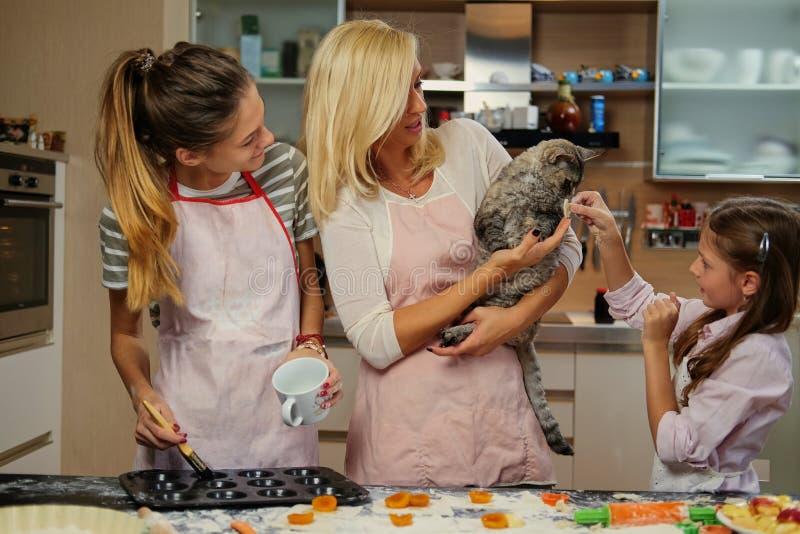 Fostra undervisa hennes döttrar hur man förbereder degen arkivbild