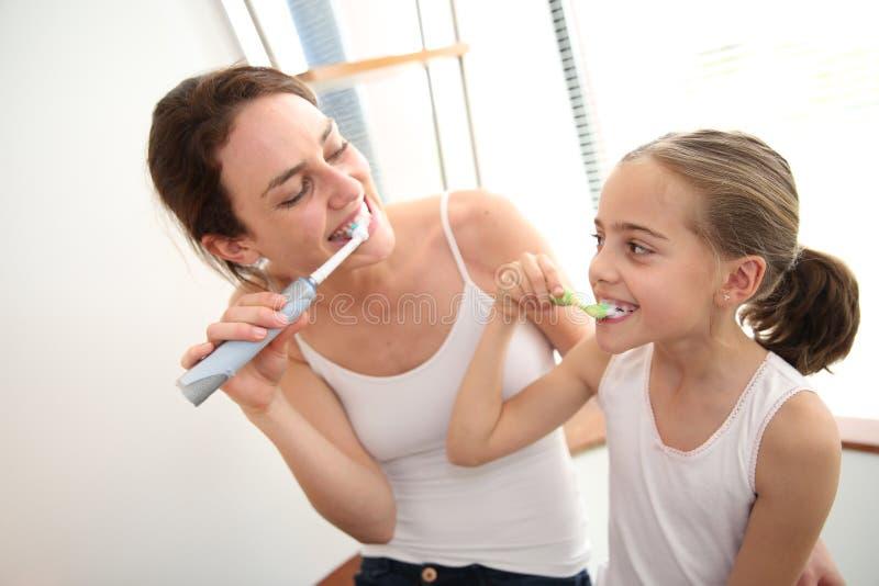 Fostra undervisa hennes dotter hur man borstar tänder royaltyfria bilder