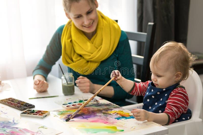 Fostra undervisa hennes lilla dotter hur man målar med vattenfärgen royaltyfria foton