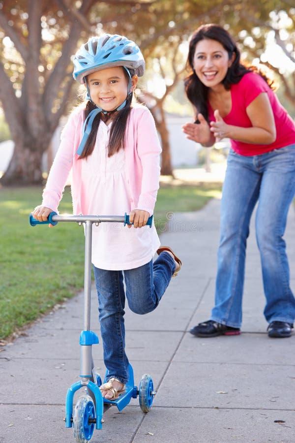 Fostra undervisningdottern för att rida sparkcykeln royaltyfria bilder
