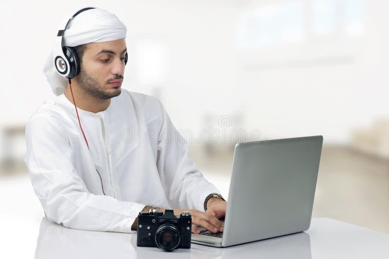 Fotógrafo árabe novo que trabalha em seu portátil imagens de stock royalty free
