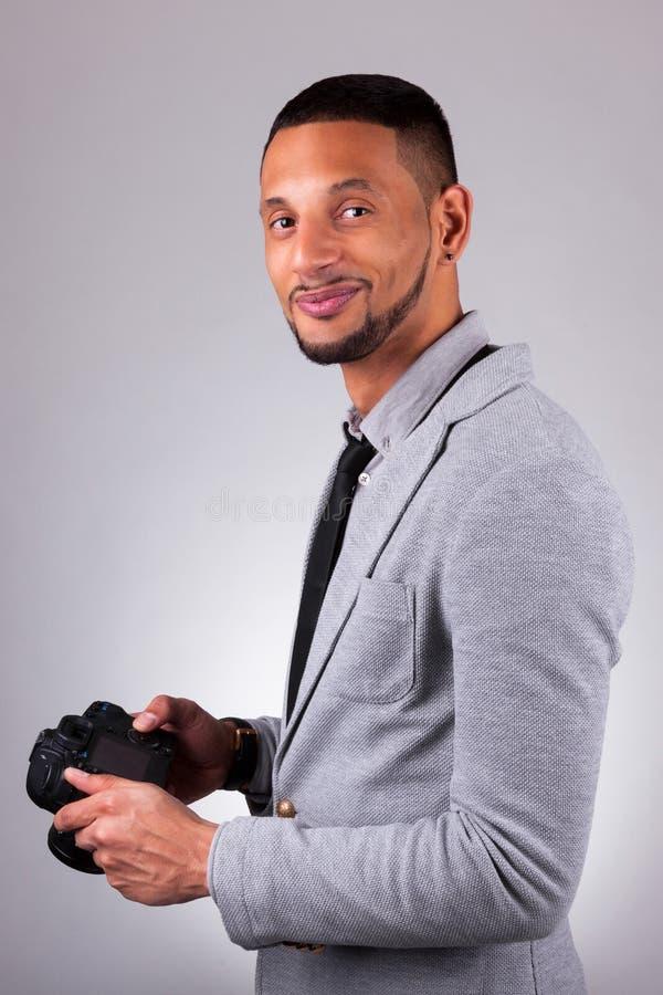 Fotógrafo afro-americano que guarda uma câmera do dslr - peop preto imagens de stock royalty free