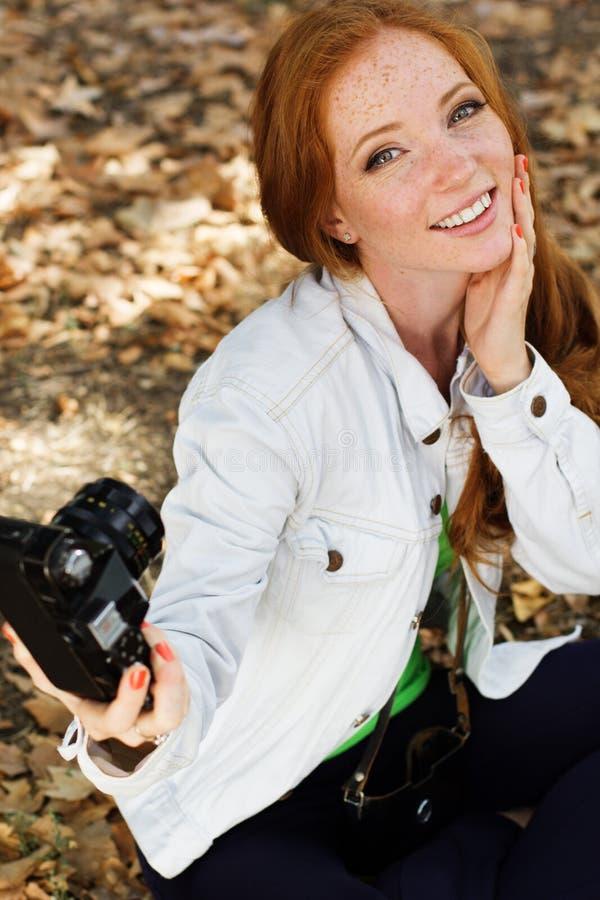 Fotógrafo agradable de la muchacha que toma el selfe en parque del otoño foto de archivo libre de regalías