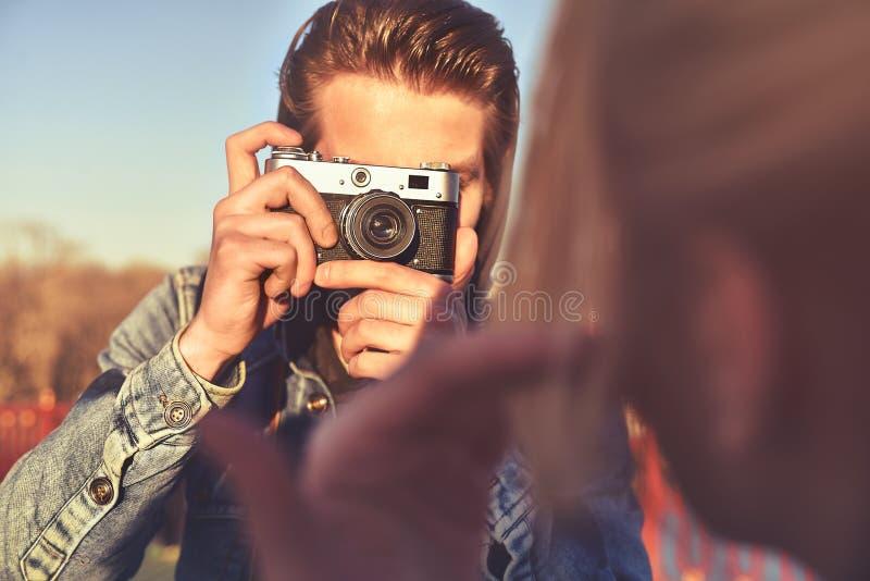 Fotógrafo alegre novo do homem que toma imagens com câmera foto de stock royalty free