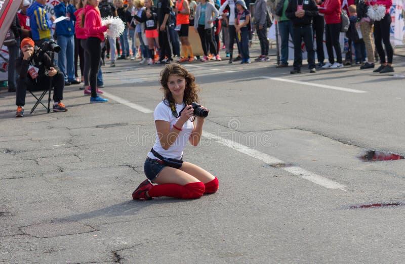 Fotógrafo amador fêmea bonito que senta-se em uma rua e que espera uma estação de acabamento para para fazer o tiro fresco fotografia de stock royalty free