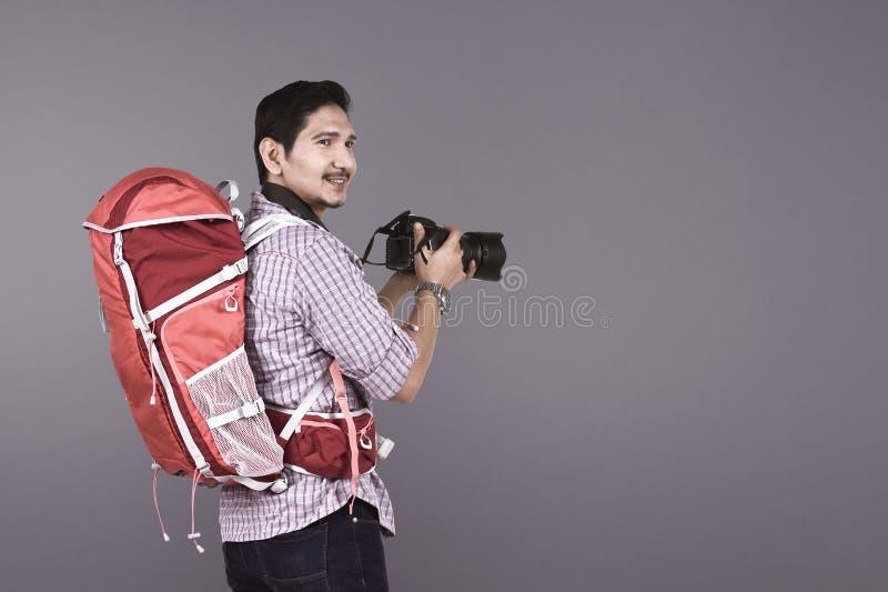 Fotógrafo asiático joven con la mochila que sostiene la cámara imagen de archivo
