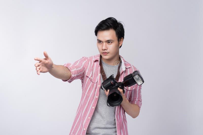 Fotógrafo asiático joven que sostiene la cámara digital, mientras que trabaja i fotos de archivo libres de regalías