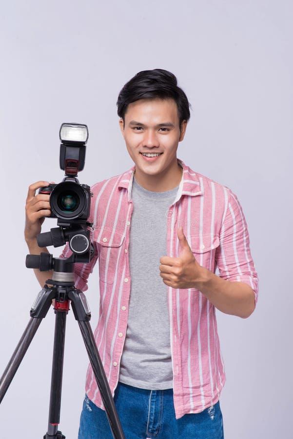 Fotógrafo asiático novo que guarda a câmara digital, ao trabalhar i fotografia de stock royalty free