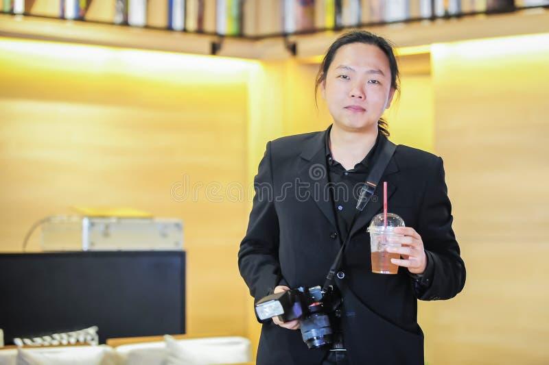 Fotógrafo asiático relajante que sostiene la bebida y la cámara fotografía de archivo libre de regalías