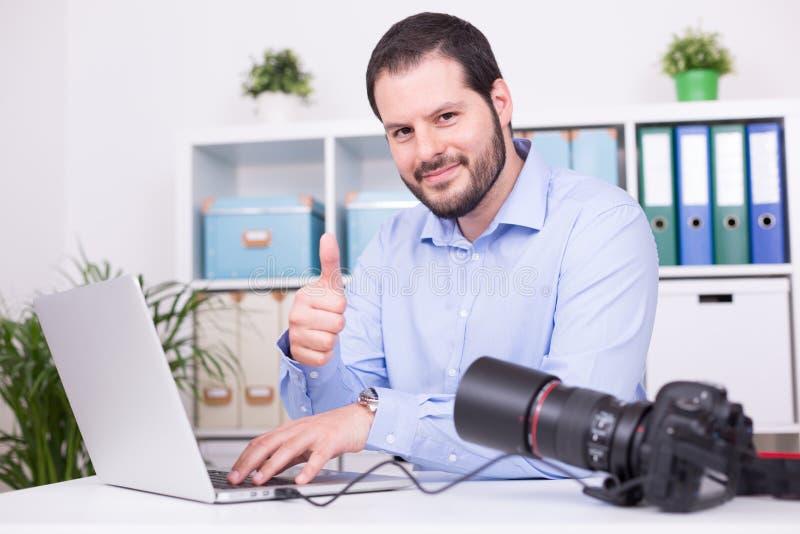 Fotógrafo barbudo en su oficina con el ordenador portátil y la cámara foto de archivo