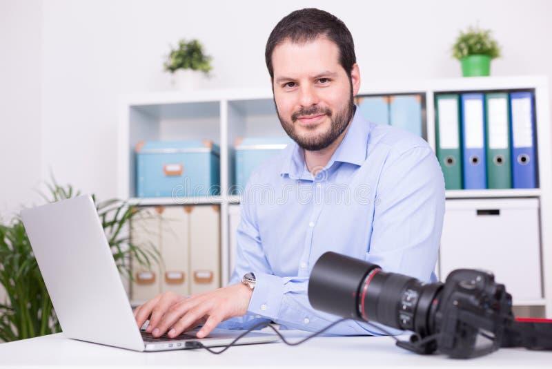 Fotógrafo barbudo en su oficina con el ordenador portátil y la cámara fotografía de archivo libre de regalías