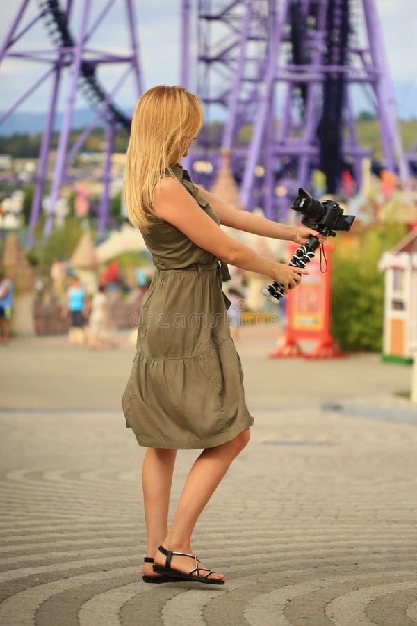 Fotógrafo bonito da mulher que toma-se com uma câmera em um parque de diversões Um blogger feliz faz uma imagem engraçada fotos de stock royalty free