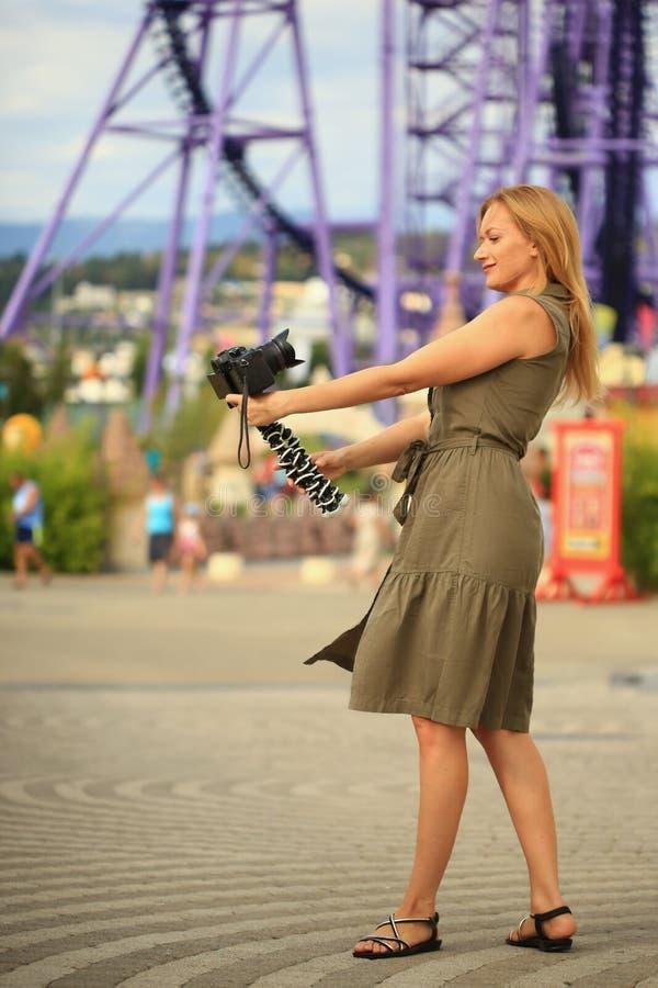 Fotógrafo bonito da mulher que toma-se com uma câmera em um parque de diversões Um blogger feliz faz uma imagem engraçada foto de stock royalty free