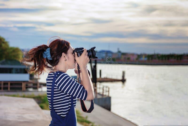 Fotógrafo bonito que toma uma foto perto de Chao Phraya River dentro imagens de stock