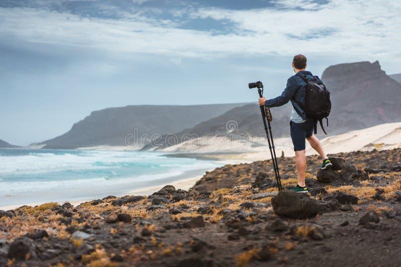 Fotógrafo com a câmera no tripé no deserto que admite a paisagem original de penhascos vulcânicos das dunas de areia no Atlântico imagem de stock royalty free