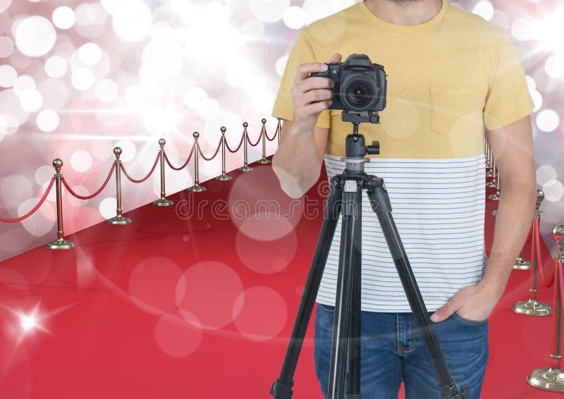 fotógrafo com a câmera no tripé no tapete vermelho Fundo e alargamentos vermelhos e brancos do bokeh nunca imagens de stock