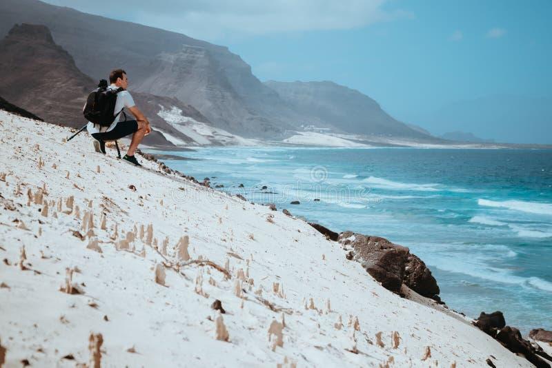 Fotógrafo com câmera que aprecia o momento catita na paisagem litoral cênico de dunas de areia e de penhascos vulcânicos Baia DAS fotografia de stock