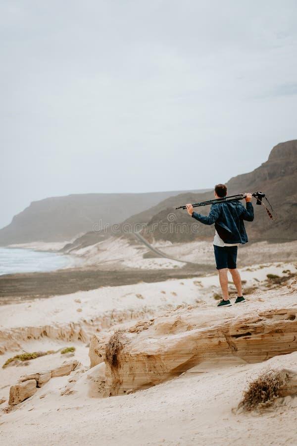 Fotógrafo com a câmera que procura o motriz da paisagem original Dunas de areia e penhascos vulcânicos no Atlântico imagens de stock royalty free