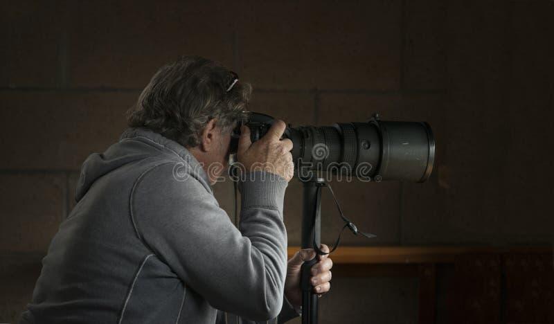 Fotógrafo com a lente teleobjetiva no monopod imagens de stock royalty free