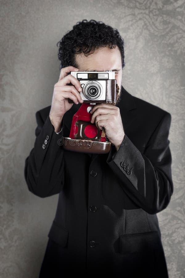 Fotógrafo com o terno preto no fundo do vintage com câmera velha fotografia de stock royalty free