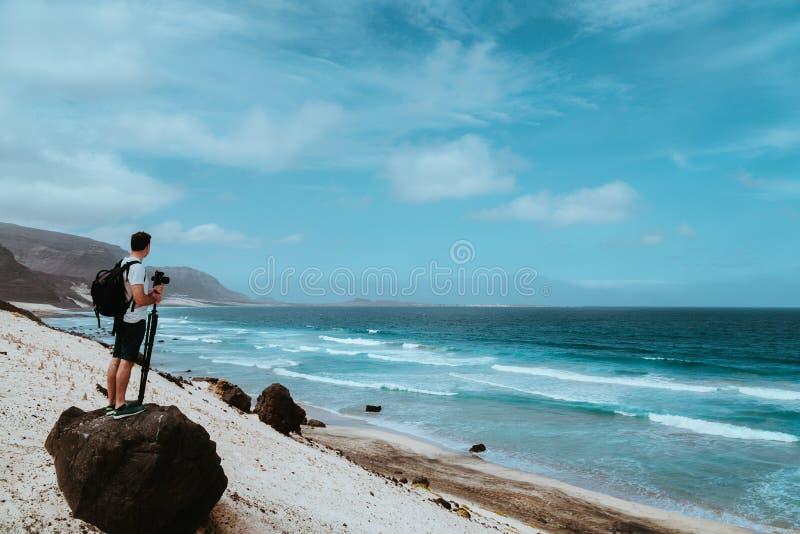 Fotógrafo com stative e câmera que ficam na rocha e que apreciam a paisagem litoral de dunas de areia, penhascos vulcânicos fotografia de stock