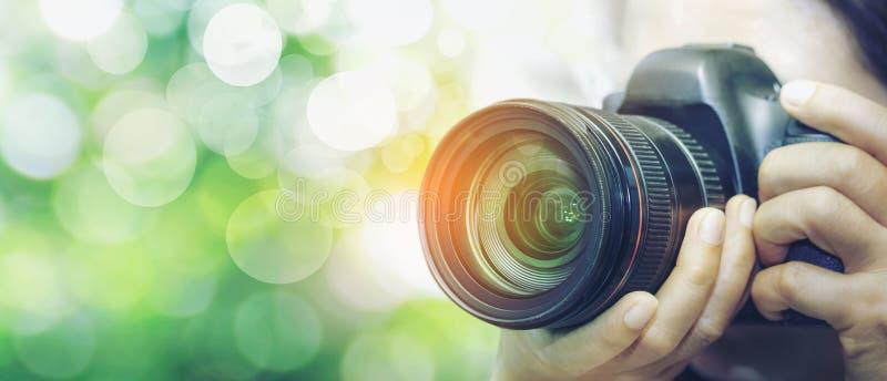 Fotógrafo con la cámara a disposición que mira a través de la lente de cámara foto de archivo