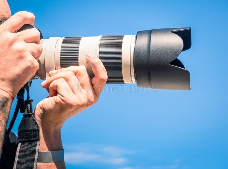 Fotógrafo con la lente digital del enfoque grande imagenes de archivo