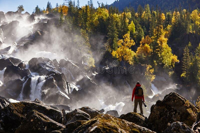Fotógrafo con la mochila que goza sorprendiendo vacaciones de la forma de vida del viaje de la cascada y del concepto del éxito e imagen de archivo libre de regalías