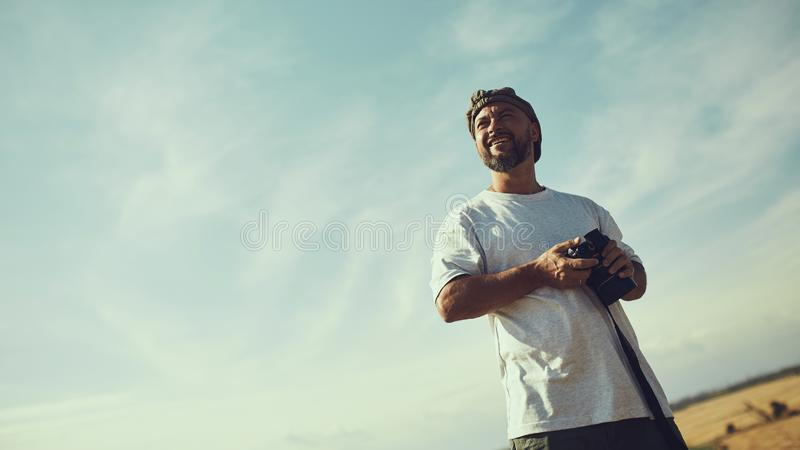 Fotógrafo con una cámara en sus manos contra el cielo en un día caliente, bochornoso Lugar para el texto, fondo, papel pintado fotografía de archivo