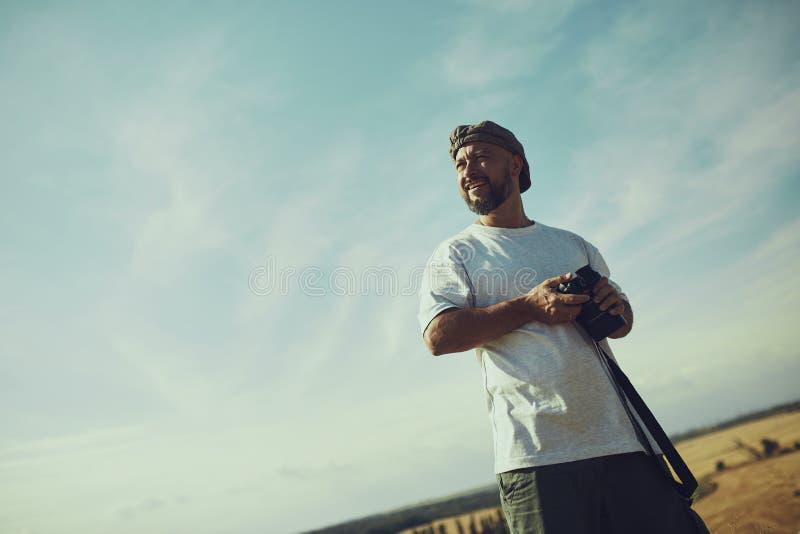 Fotógrafo con una cámara en sus manos contra el cielo en un día caliente, bochornoso Lugar para el texto, fondo, papel pintado imagenes de archivo