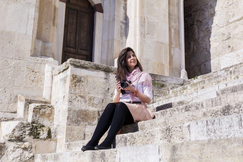 Fotógrafo da jovem mulher que toma as fotos que sentam no as escadas de pedra fotografia de stock