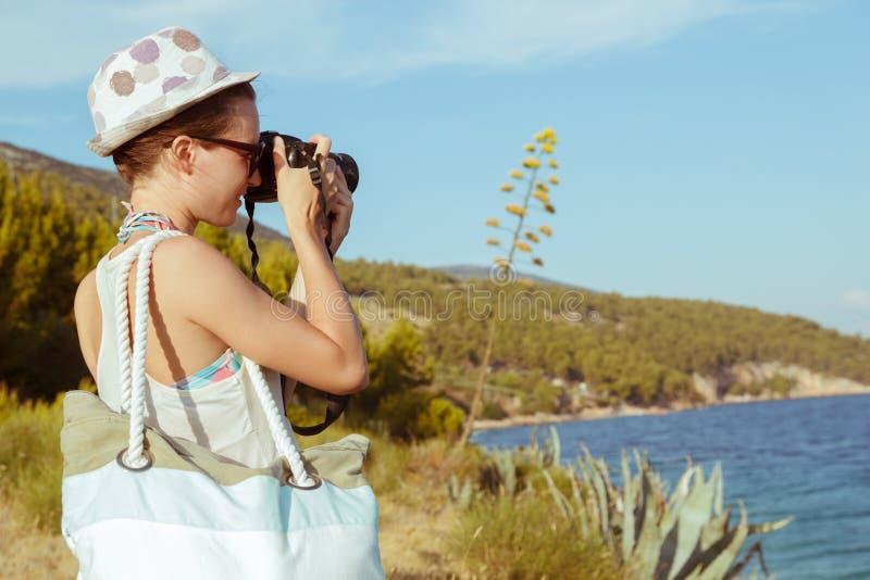 Fotógrafo da jovem mulher, turista que usa a câmara digital que toma a foto pelo mar fotografia de stock