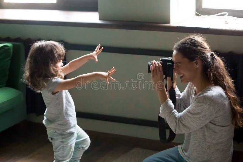 Fotógrafo da mamã que faz a foto da filha da criança na câmara digital foto de stock