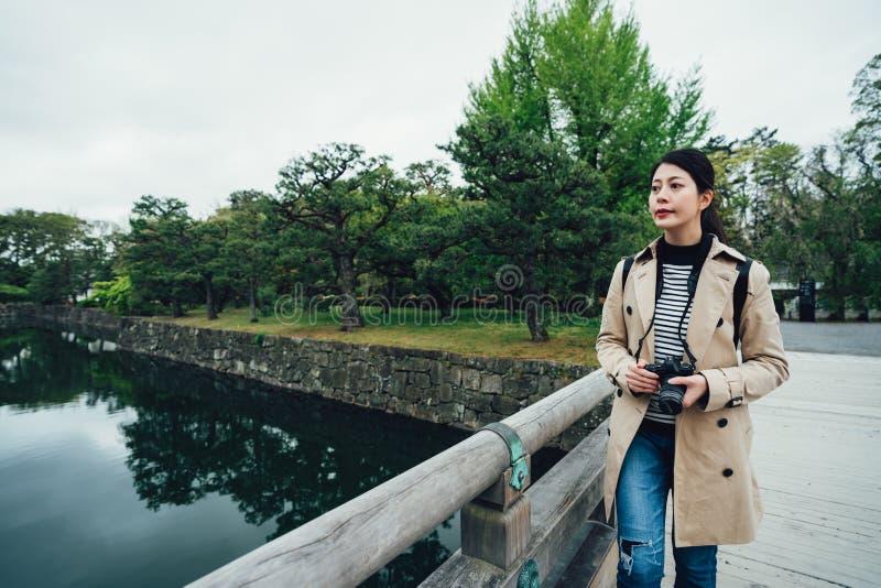 Fotógrafo de la chica joven que camina en el puente de madera fotos de archivo