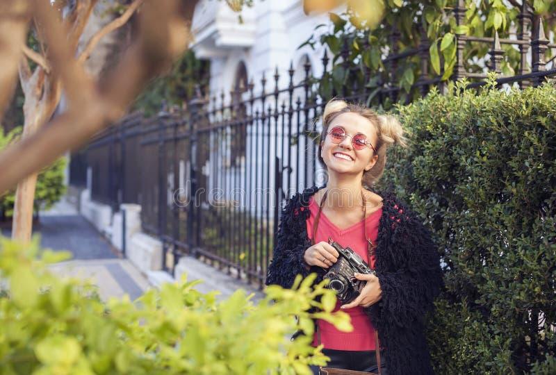 Fotógrafo de la muchacha que lleva a cabo la cámara antigua y la risa imagenes de archivo