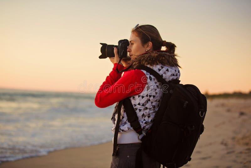 Fotógrafo de la muchacha que toma imágenes con la cámara de SLR imagen de archivo