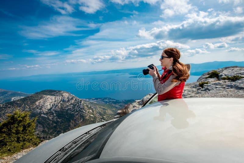 Fotógrafo de la mujer con el coche en el top de la montaña imagen de archivo