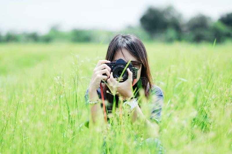 Fotógrafo de la mujer joven del retrato de la vista delantera que sostiene la cámara y imagenes de archivo