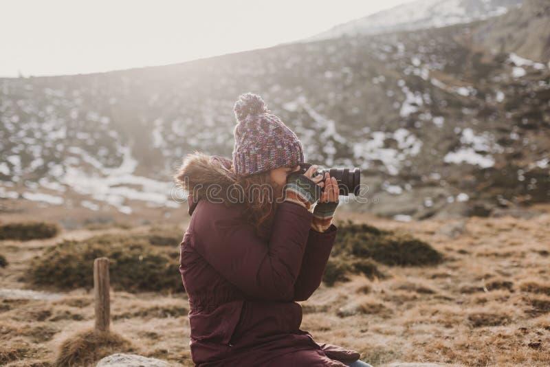 fotógrafo de la mujer joven que toma la foto en el pico de montaña y que sonríe en la puesta del sol fotos de archivo libres de regalías