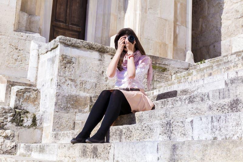 Fotógrafo de la mujer joven que toma las fotos que sientan en las escaleras de piedra imagen de archivo