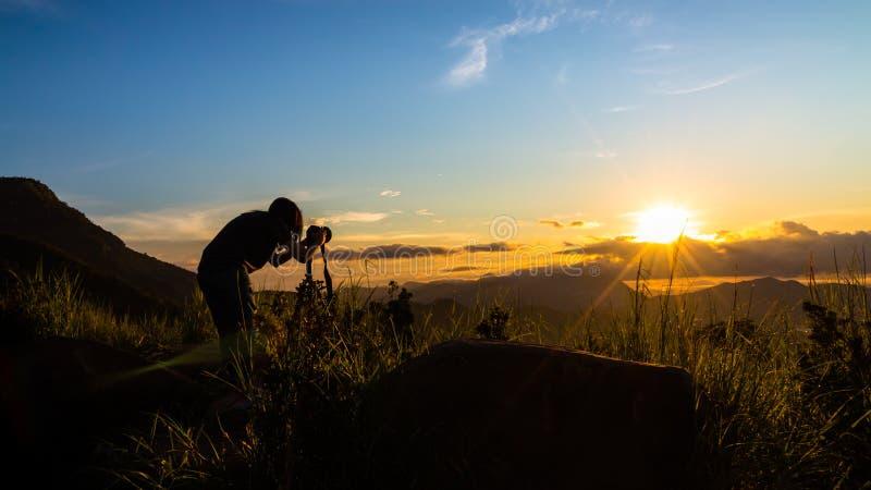 Fotógrafo de la mujer y salida del sol hermosa fotografía de archivo