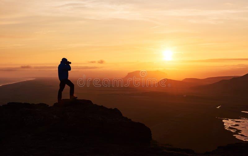 Fotógrafo de la naturaleza con la cámara digital encima de la montaña imagenes de archivo