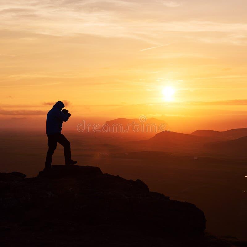Fotógrafo de la naturaleza con la cámara digital encima de la montaña imágenes de archivo libres de regalías