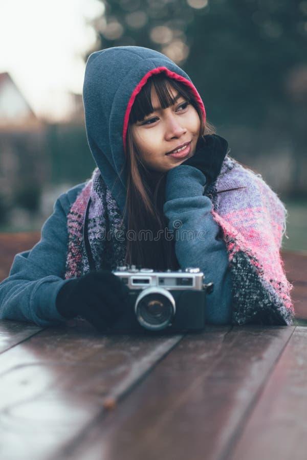 Fotógrafo de sexo femenino de moda en el tiempo frío que lleva la bufanda y la chaqueta coloridas con el casquillo imagen de archivo