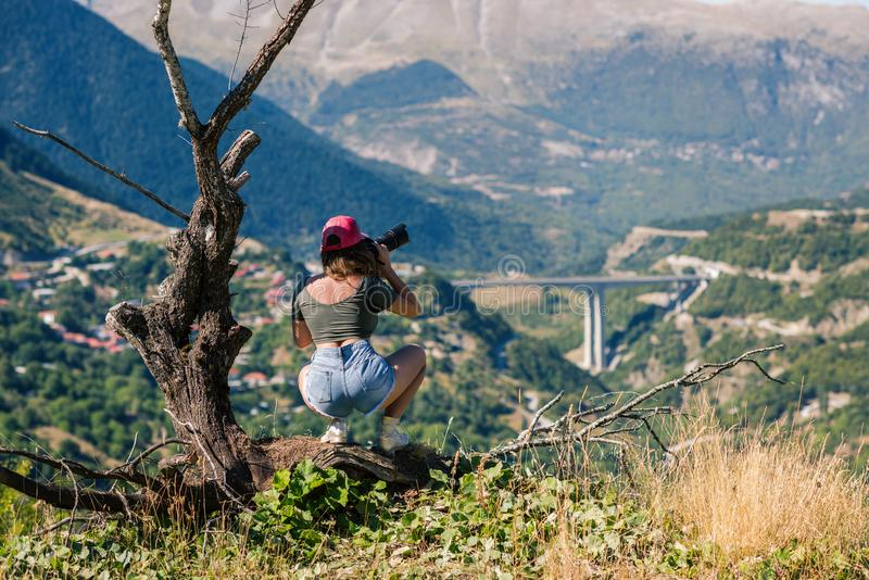 Fotógrafo de sexo femenino joven con la cámara profesional cerca del árbol viejo grande enfrente del pueblo griego Una muchacha c imagenes de archivo