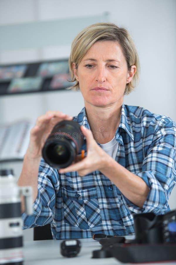 Fotógrafo de sexo femenino que elige la cámara para el trabajo fotos de archivo libres de regalías