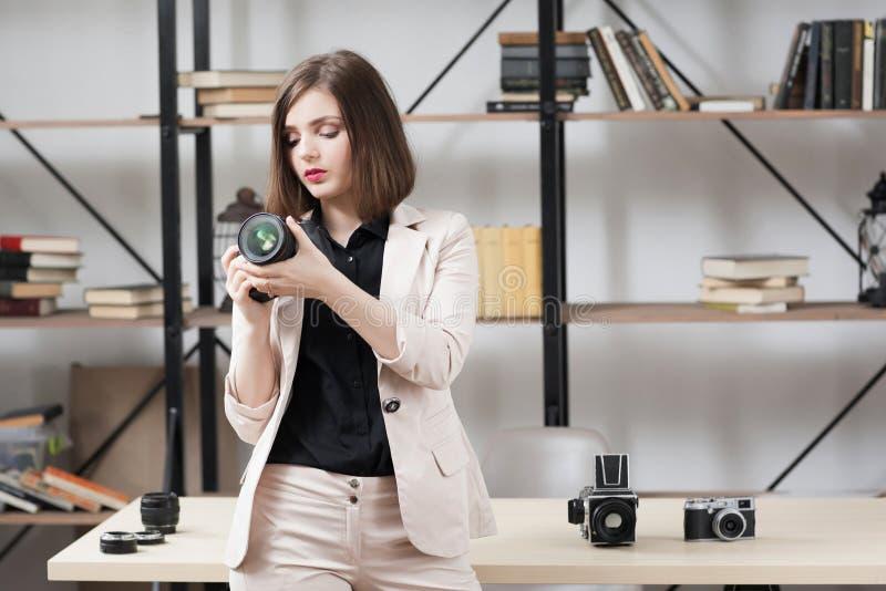 Fotógrafo de sexo femenino que elige la cámara para el trabajo fotos de archivo