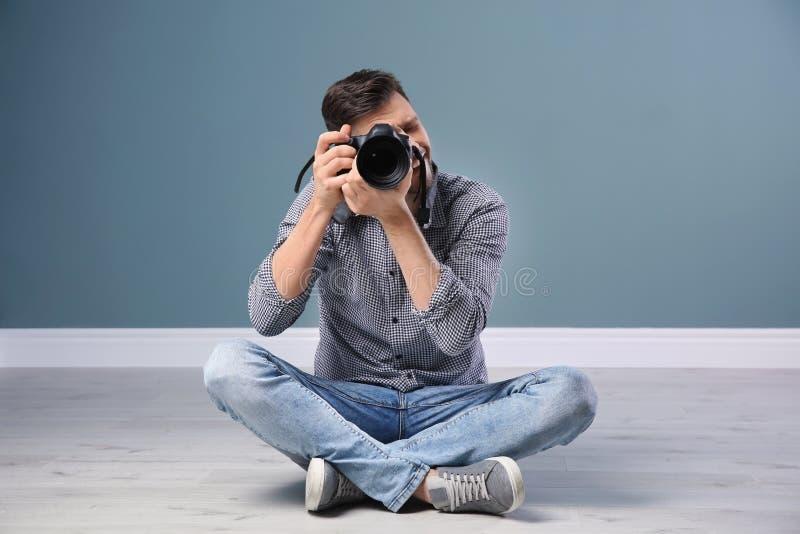 Fotógrafo de sexo masculino con la cámara cerca de la pared imágenes de archivo libres de regalías