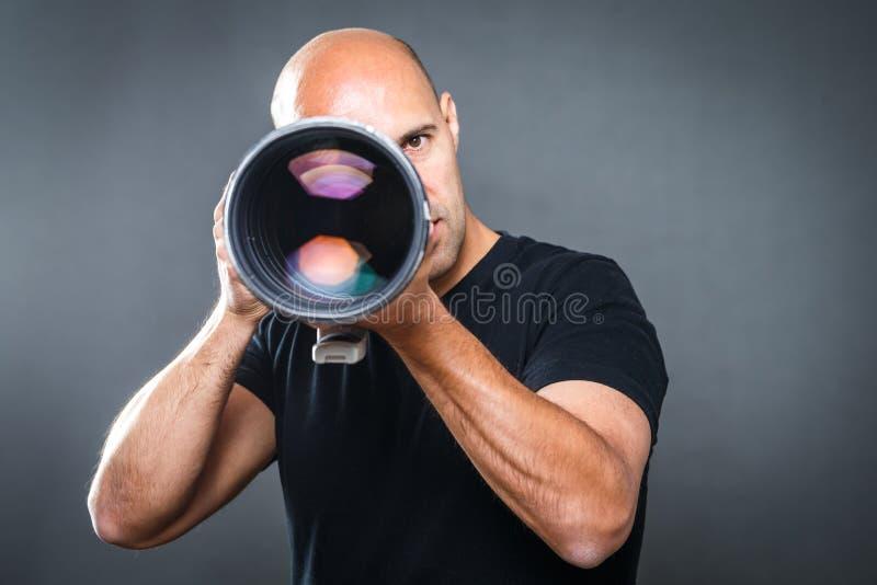 Fotógrafo de sexo masculino joven, favorable en su estudio foto de archivo libre de regalías