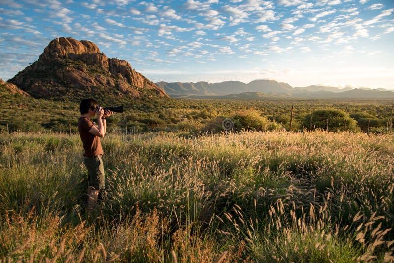 Fotógrafo de sexo masculino joven que toma la foto de la salida del sol en woodl de la sabana imagen de archivo